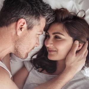 Paar mittleres Alters liegt im Bett und schaut sich in die Augen