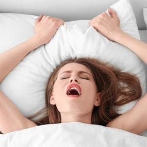 Junge schöne Frau im Bett, die Intimität genießt