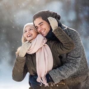 Junge Frau und Mann umarmen sich draussen im Winter